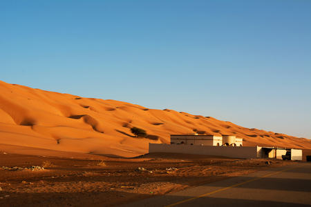 Residential building under the desert dunes wahiba sands at sunset (Oman) Editorial