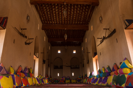 Living room with carpet, cushions and weapons in Nakhal Fort (Oman)