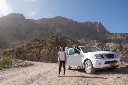 Off-road vehicle and tourists on the Jebel Shams mountains (Oman)