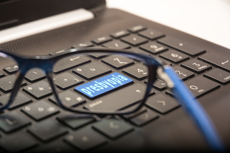 View of the PC keyboard through the lens of the glasses on the button with the written Presbyopia Stock Photo