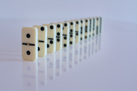 domino tiles in a row on white background in Low key Stock Photo