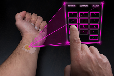 Holographic telephone keypad projected by the implanted SIM under the skin Stock Photo