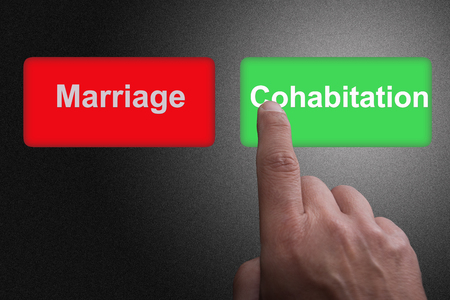 Buttons with written marriage and cohabitation and pointing finger, on a gray gradient background Фото со стока