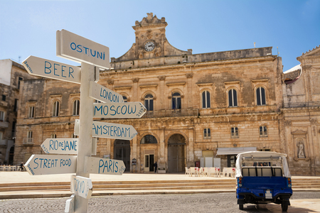 Tourist signpost with distances and in the background the Municipality of Ostuni (Italy)