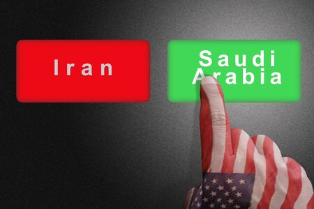Hand with the colors of the American flag chooses Saudi Arabia against Iran: concept of US political support for Saudi Arabia against Iran