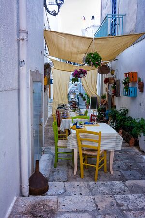 Restaurant tables set for dinner in an alleyway of Ceglie messapica in Puglia (Italy) Banco de Imagens