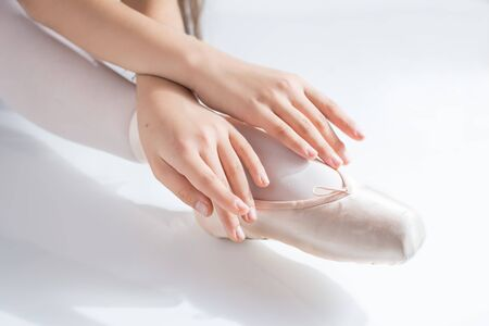 close-up of feet with pink satin pointe shoes and the hands of a classical dancer posing