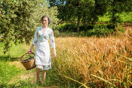 Woman in 40s clothes walks in the Italian countryside, next to a wheat field, carrying a basket of cherries 版權商用圖片