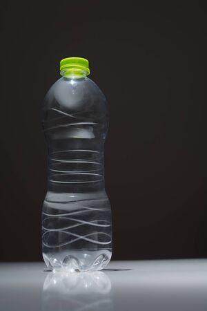 Empty plastic bottle in transparent PET on a dark background Фото со стока