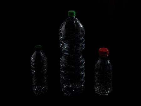 Plastic bottle in transparent PET on a dark background 版權商用圖片