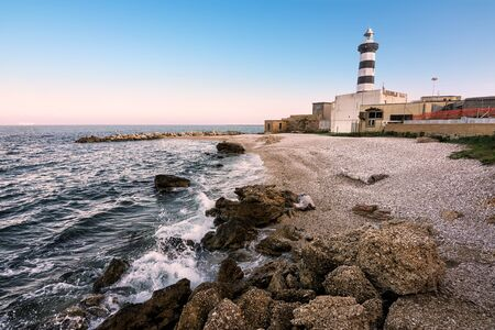 The Faro di Ortona and its pebble beach at sunset