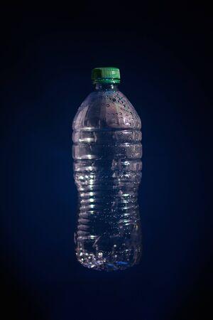 Silueta de botella de plástico transparente utilizada sobre fondo oscuro Foto de archivo