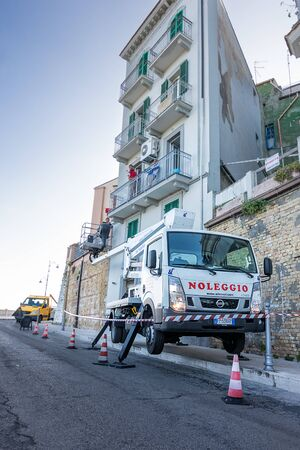 Ortona, Italy - 26 october 2019: truck with basket for work on buildings with workers at work in Ortona