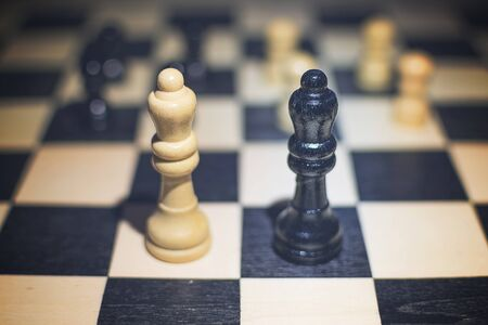 the chessboard with  Black Queen and white Queen in front in the concept of agreement and pawns in the background Stock Photo
