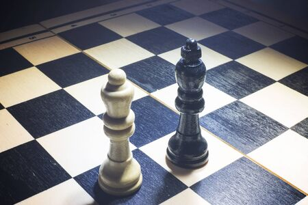 the chessboard with the Black king and white queen facing in understanding concept