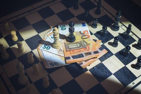 Top view of chessboard with arranged pieces, money with queens on top, agreement concept Banco de Imagens
