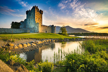 Ancient old Fortress Ross Castle ruin with lake and grass in Ireland during golden hour nobody