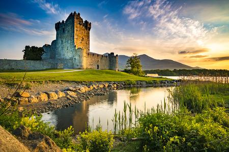 Starożytne ruiny zamku Ross Castle z jeziorem i trawą w Irlandii podczas złotej godziny nikt Zdjęcie Seryjne