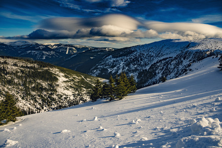 Amazing view on mountain range with snow, trees and beautiful blue sky with clouds