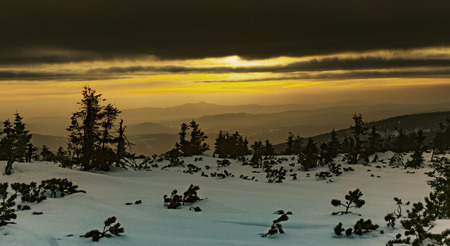 Mountain slope covered with snow and trees, setting sun covered with cloud Stock Photo