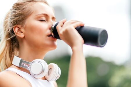 Drink it. Fitness girl having workout outdoors. Copy space in lower right part