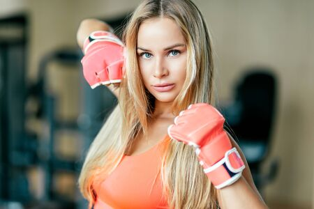 Don't mess with me. Attractive female kickboxer having workout in gym. Copy space on the right and on the left side