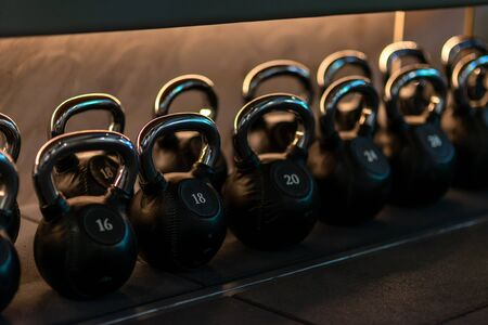 For you to choose. Stylish kettlebells weights made of black leather and iron lying in a row on the shelf in workout gym. Sport, lifting, healthy lifestyle concept. Horizontal shot. Archivio Fotografico