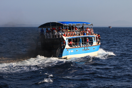 A tourist boat producing black smoke and polluting the sea, during a whale watching tour. Editorial
