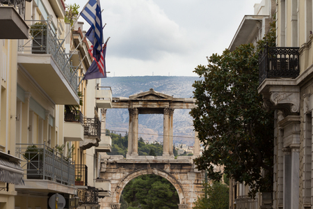 A historical monument seen behind modern buildings in the center of Athens Stock Photo