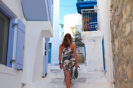 A girl with her back turned, walking in one of the small streets of a Greek island Stockfoto