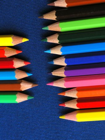 Colored Pencils in a Row on blue background photo