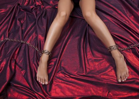 Woman Legs In Chains On Red Satin Stock Photo - 5438943