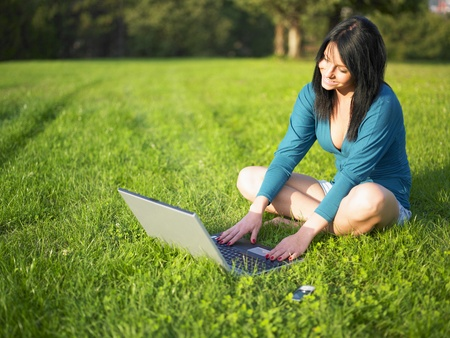 Young woman using laptop in park Stock Photo - 9423684