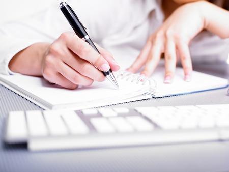 secretaria: Escritura de mujer de negocios con la pluma en el Bloc de notas Foto de archivo