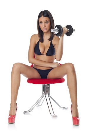 body building: Beautiful woman sitting on red chair and training with dumbbells  Stock Photo