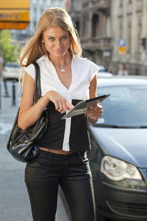 Young Beautiful Business Woman with tablet computer walking on urban street, downtown photo