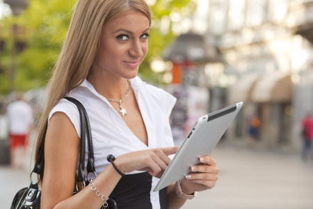 Belgrade, Serbia - September 02, 2011: Woman holding an Apple iPad in downtown street. The iPad is produced by Apple Computer, Inc. Passers-by in the background