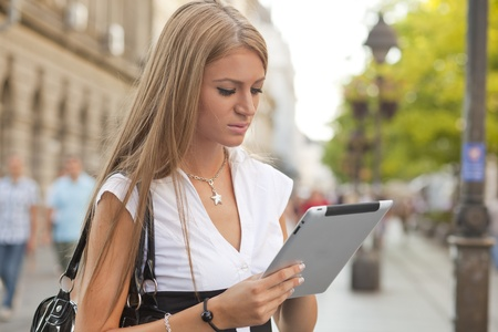 city life: Young Beautiful Business Woman with tablet computer walking on urban street, downtown Stock Photo