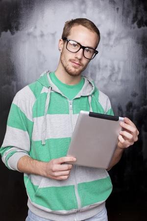 Good Looking Young Nerd Smart Guy Man Using Tablet Computer photo