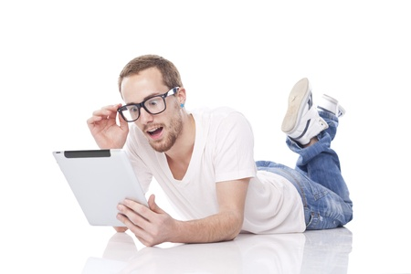 Good Looking Young Smart Man Using Tablet Computer and lying on the floor