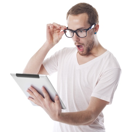 Surprised Young Nerd Smart Guy Looking At Tablet Computer photo