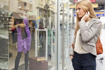 tienda de ropa: Cliente mujer shoping calle, mirando a la ventana, al aire libre Foto de archivo