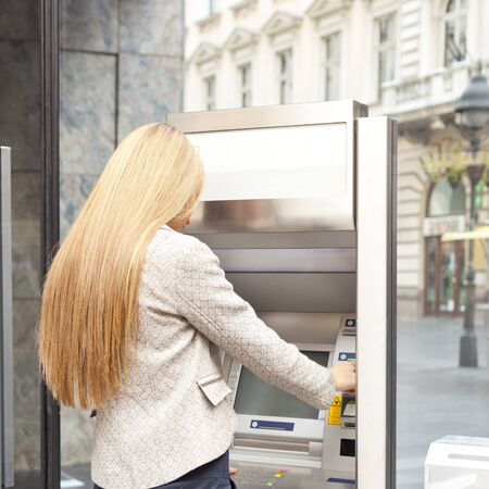 Young Woman using Bank ATM cashe machine on the street photo