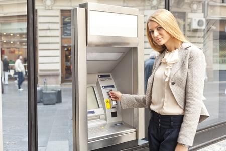 Junge Frau mit Bank ATM cashe Maschine auf der Straße Standard-Bild - 12866494