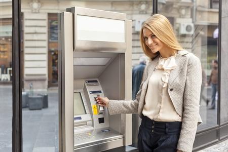 Jonge vrouw met behulp Bank ATM cashe machine op straat