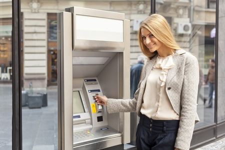 account: Young Woman using Bank ATM cashe machine on the street
