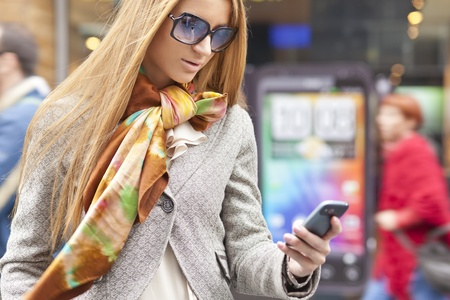 blured: Young Woman with smartphone walking on street, downtown. In background is blured street
