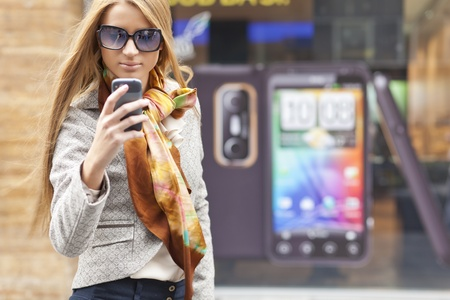 Young Woman with smartphone walking on street, downtown  In background is blured street