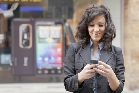 Young Woman with mobile phone walking background is blured city photo