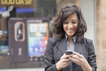 Young Woman with mobile phone walking background is blured city Stock Photo